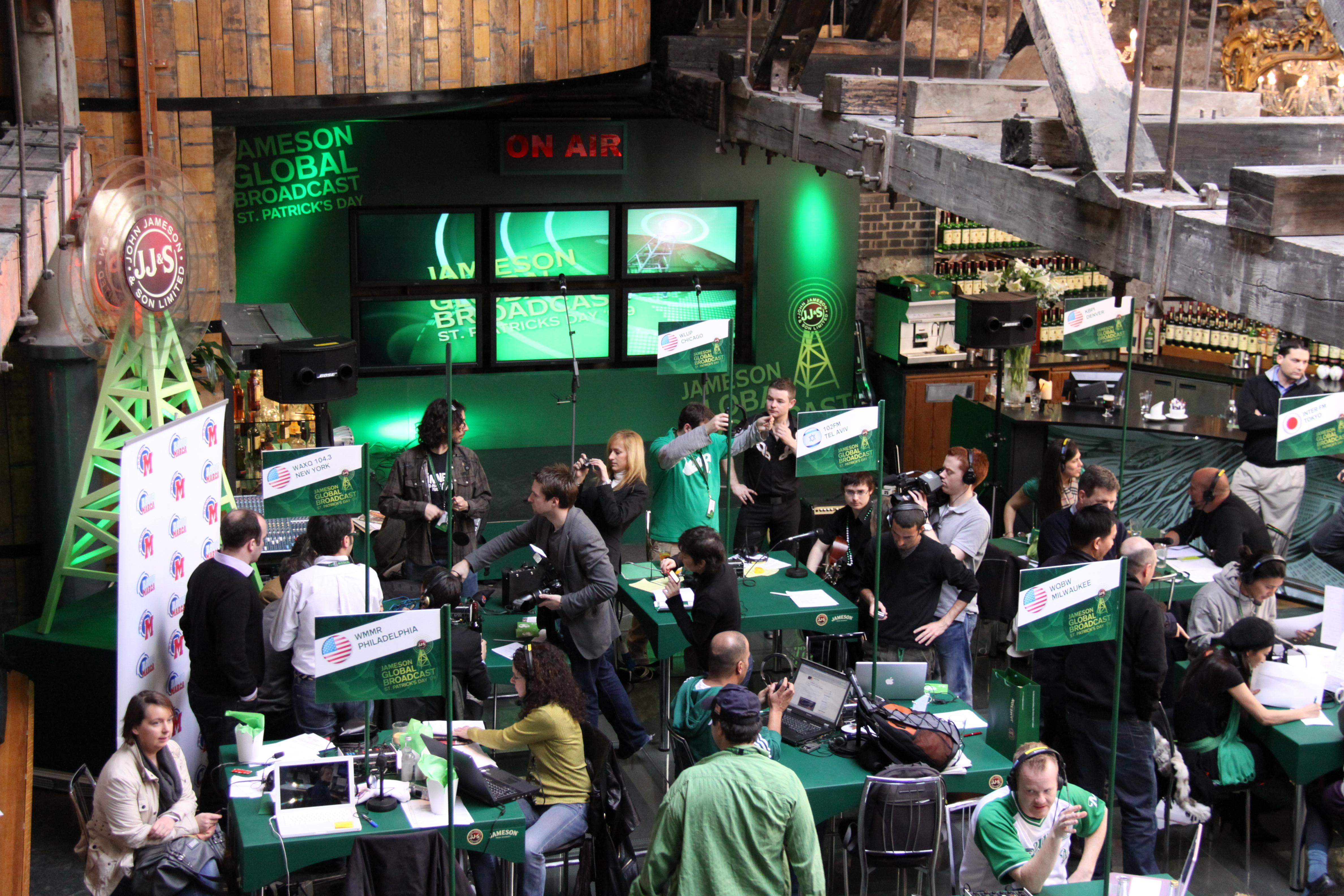 Several groups of people are gathered around tables to broadcast on the radio, nearly all are wearing green